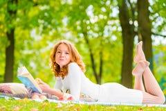 有一本好书和一棵美味苹果的浪漫女孩 库存照片