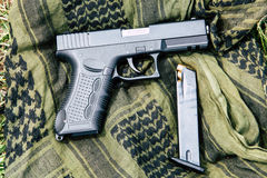 有一本杂志的一把手枪在绿色背景 免版税库存照片