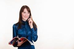 有一本杂志的女孩在他的手上谈话在电话 免版税库存照片
