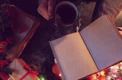 有一本空白的书的人在他的新年` s桌的手上与 免版税库存图片