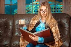 有一本红色书在手中和杯子的美丽的女孩 图库摄影