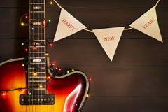 有一本被点燃的诗歌选的老电吉他在黑暗的背景 问候,圣诞节,新年贺卡 复制空间 图库摄影
