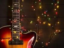 有一本被点燃的诗歌选的老电吉他在黑暗的背景 问候,圣诞节,新年贺卡 复制空间 免版税库存图片