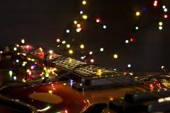有一本被点燃的诗歌选的老电吉他在黑暗的背景 问候,圣诞节,新年贺卡 复制空间 库存图片