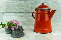 有一朵五颜六色的花的红色咖啡壶 图库摄影