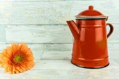 有一朵五颜六色的花的红色咖啡壶 免版税库存图片