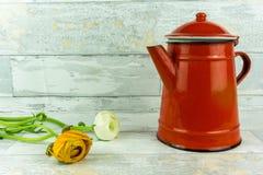 有一朵五颜六色的花的红色咖啡壶 库存图片