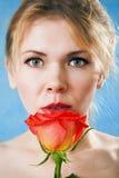 有一朵唯一红色玫瑰的新美丽的妇女 库存照片