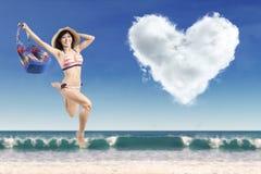 有一朵心形的云彩的夫人在海岸 库存图片