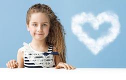 有一朵心形的云彩的小女孩 免版税库存照片
