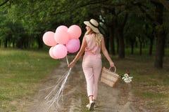 有一朵柳条筐、帽子、桃红色轻快优雅和花的妇女走在乡下公路的 免版税图库摄影