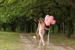 有一朵柳条筐、帽子、桃红色轻快优雅和花的妇女走在乡下公路的 库存照片