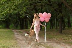 有一朵柳条筐、帽子、桃红色轻快优雅和花的妇女走在乡下公路的 库存图片