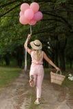 有一朵柳条筐、帽子、桃红色轻快优雅和花的妇女走在乡下公路的 免版税库存图片