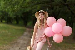 有一朵柳条筐、帽子、桃红色轻快优雅和花的妇女走在乡下公路的 免版税库存照片