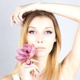 有一朵桃红色花的可爱的美丽的金发碧眼的女人 有永久构成的妇女 妇女的接近的纵向 免版税库存照片