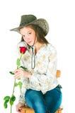 有一朵玫瑰的女孩在牛仔帽 免版税图库摄影