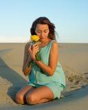 有一朵玫瑰的妇女在沙子 库存照片