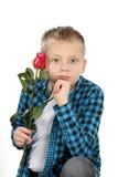 有一朵玫瑰的沉思年轻男孩在情人节 免版税库存图片