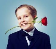 有一朵玫瑰的男孩在他的牙 库存照片