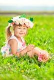 有一朵玫瑰的美丽的小女孩在他的手和ro花圈上  图库摄影
