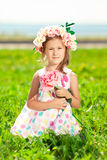 有一朵玫瑰的美丽的小女孩在他的手和ro花圈上  免版税图库摄影