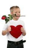有一朵玫瑰的年轻男孩在他的嘴 库存照片