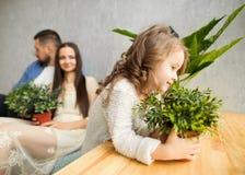 有一朵生长花的小女孩在看她的手上  免版税库存照片