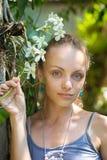 有一朵白色兰花的分支的女孩 免版税图库摄影
