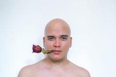 有一朵红色玫瑰的一个人在他的嘴 免版税库存图片