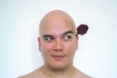 有一朵红色玫瑰的一个人在他的嘴 库存图片
