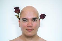 有一朵红色玫瑰的一个人在他的嘴 免版税库存照片