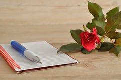 有一朵红色玫瑰的一个笔记本 免版税库存照片