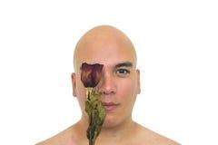 有一朵红色玫瑰的人在他的眼睛 库存图片