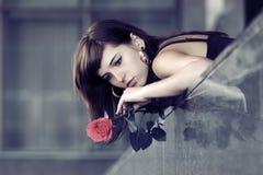 有一朵红色玫瑰的哀伤的少妇 免版税库存图片