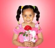有一朵红色玫瑰的微笑的小女孩 免版税库存图片