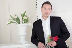 有一朵红色玫瑰的浪漫人 图库摄影