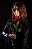 有一朵红色玫瑰的美丽的少妇在黑皮夹克 免版税库存照片