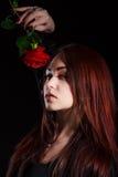 有一朵红色玫瑰的美丽的少妇 图库摄影