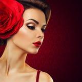 有一朵红色花的热情的夫人在她的头发。 库存照片
