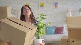 有一朵花和一个箱子的正面年轻西安妇女在他的手上移动向一栋新的公寓 股票视频