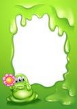 有一朵花的一个绿色妖怪在一块空的模板前面 库存图片
