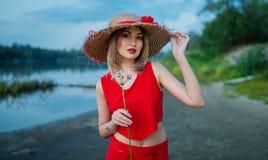有一朵花的女孩在一件红色礼服和一个草帽在河岸在晚上末期 免版税库存图片
