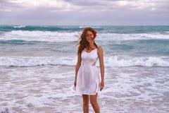 有一朵花的女孩在她的头发沿海滩走在海洋附近 免版税库存图片