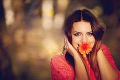 有一朵花的女孩在他的嘴 免版税图库摄影