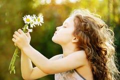 有一朵花的小女孩在她的手上 免版税库存照片