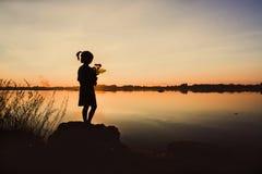 有一朵花的小女孩在他的手上 给某人,剪影 库存照片