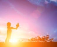 有一朵花的小女孩在他的手上 给某人,剪影 免版税库存照片