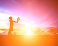 有一朵花的小女孩在他的手上 给某人,剪影 免版税库存图片