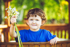有一朵花的小孩子在她的手上 库存照片
